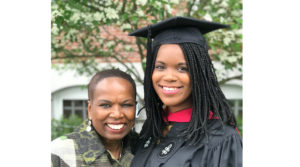 Judy Belk and daughter Casey, wearing graduation cap, face the camera, smiling.